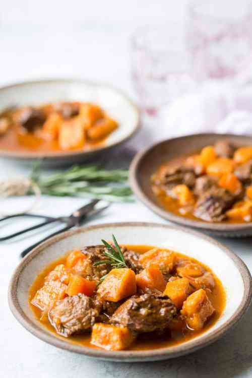 three white bowl with slow cooker beef stew on a white background with spoons and rosemary in the shot