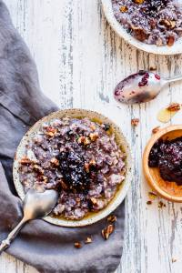 a straight down shot of a bowl of blueberry crisp oatmeal with a silver spoon in it on the left and a blue-gray towel underneath. a wooden bowl with blueberry jam is to the right, with another bowl of oatmeal in the upper right. Another silver spoon rests between the jam bowl and the secondary bowl.