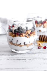 a front shot of a stemless wine glass with breakfast yogurt parfait in it. parfait consists of alternating layers of vanilla yogurt, granola, and blueberries and pomegranate seeds. Another parfait is in the right background and a white towel with thin black outlined squares is the left background. A honey stick lies to the right on the ground, with honey pooling near it.