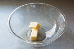 a halved stick of butter in a large, clear microwavable bowl