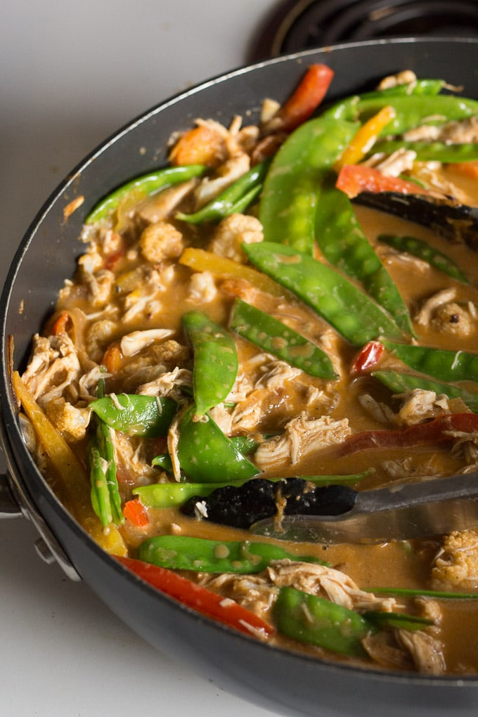 chicken curry zoodle ingredients in a pan with tongs