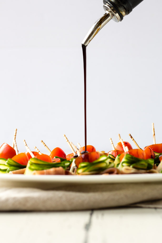 a side shot of aged balsamic vinegar being poured on a white platter with cucumber bites on it