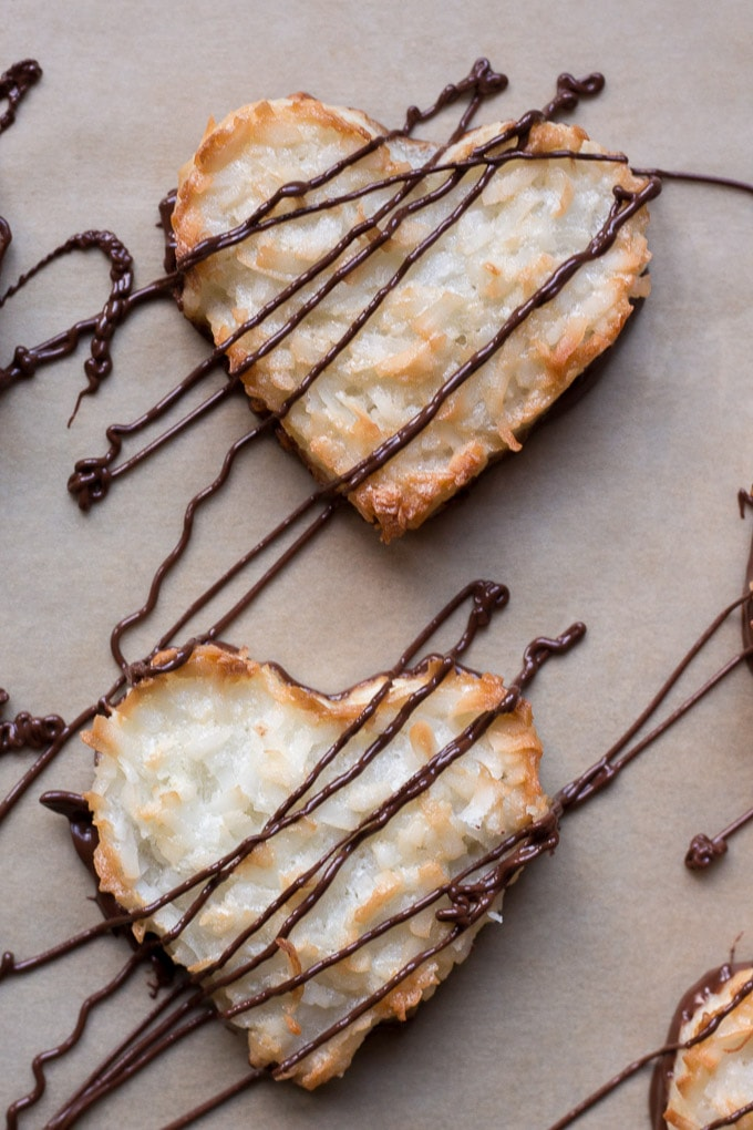 top down view of chocolate drizzled on top of gluten free coconut macaroons in heart shapes on parchment paper