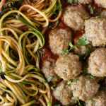top down view of baked paleo turkey meatballs in marinara with zucchini noodles