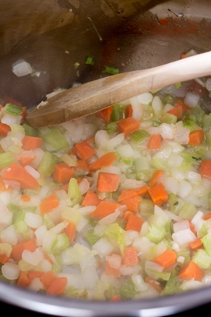 mirepoix mix being cooked in an Instant Pot with a wooden spoon