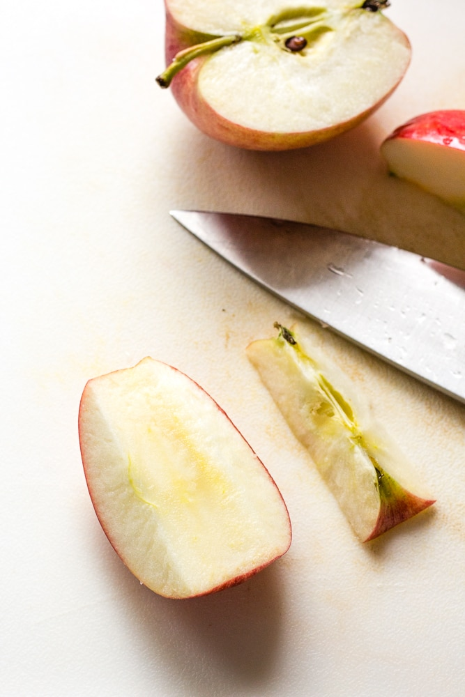 a cut apple on a white cutting board