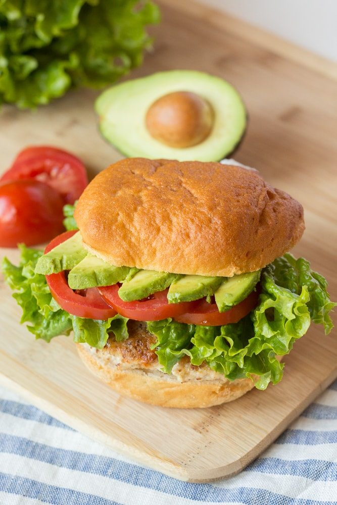 a healthy ground chicken burger on a cutting board with fixings in the background