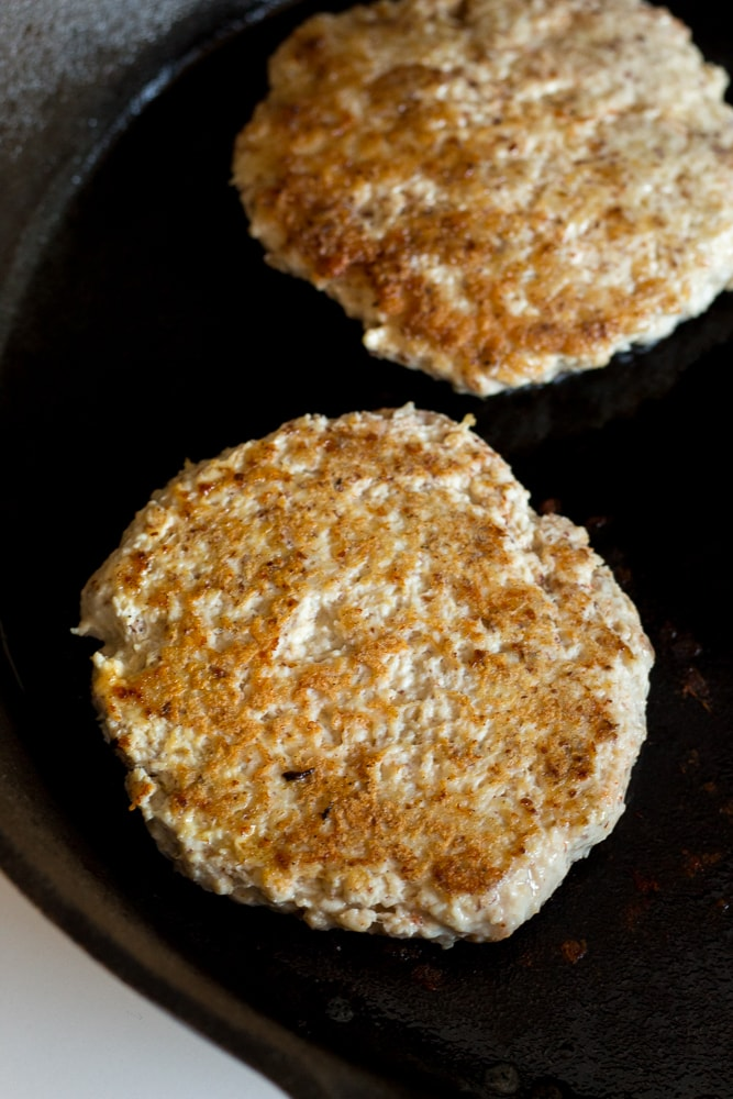a healthy ground chicken burger flipped over and cooking in a cast iron skiller