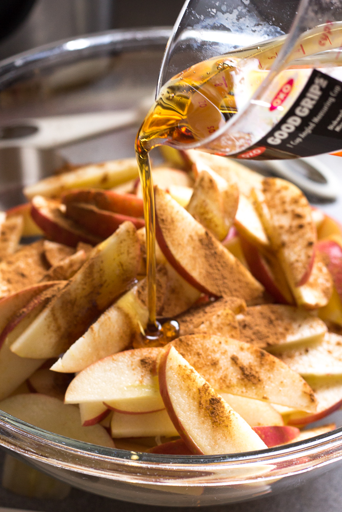 maple syrup being poured over a bowl of sliced apples