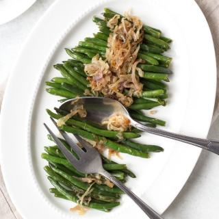 green beans on a white platter with serving utensils