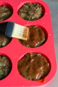 brushing ketchup on paleo meatloaf muffins