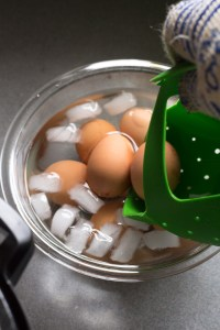 placing cooked eggs in ice bath