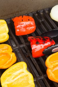 a pair of tongs flipping over grilled bell peppers