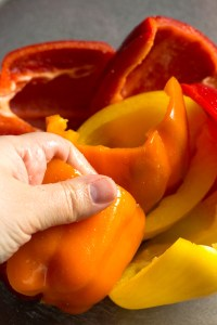a hand rubbing seasoning into halved bell peppers in a clear bowl