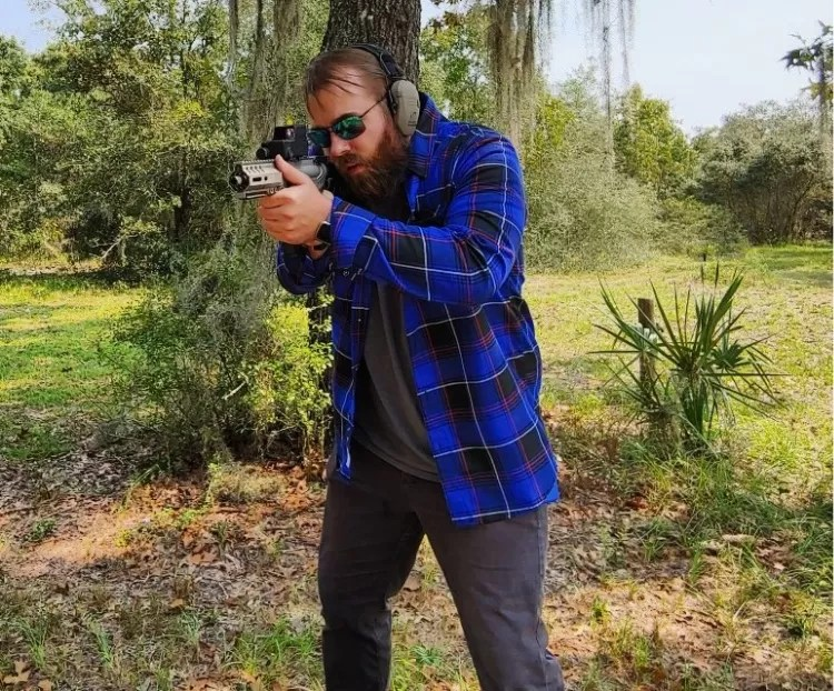 Travis Pike wearing a flannel shirt, aiming a CMMG Banshee.
