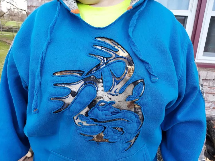 closeup of deerhead design on Legendary Whitetails Realtree camo hoodie.