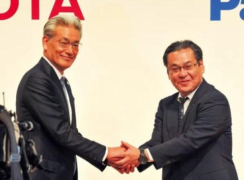 両社の代表ががっちり握手