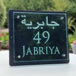 glass and slate house sign engraved with the number 49 and Jabriya in Trajan typeface including Arabic script