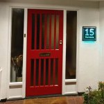 red front door with glass side panels featuring an illuminated glass house sign engraved with the number fifteen and Ferndale