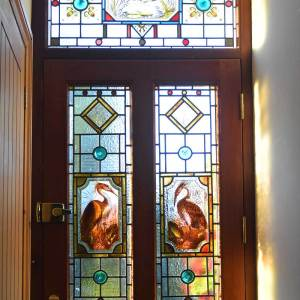 Adapted restored repaired completed stained glass door panels to match transom