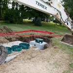 The septic tank with the pump and excavator.