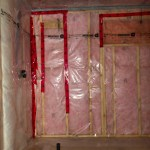 Insulation and shower plumbing in the bathroom.