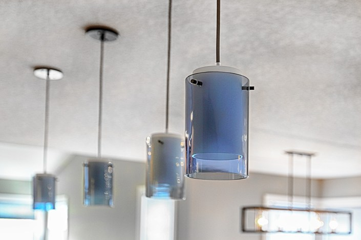 Clear blue glass pendant lights over the island. By House of J Interior Design. Edmonton, Alberta.