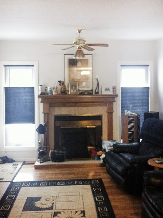 Before photo of family room. Dated fireplace, old ceiling fan.