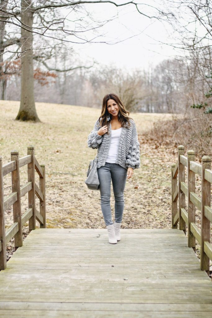 Old Navy Rockstar Jeans featured by top US fashion blog, House of Leo: image of a woman wearing a Goodnight Macaroon chunky cardigan, Steve Madden booties, Express tank and BP tassel earrings.