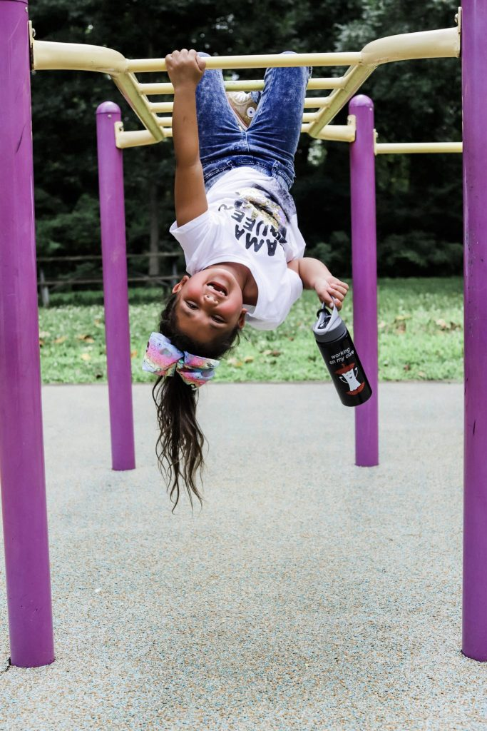Back to School Shopping With Stage Stores by top US fashion blog, House of Leo Blog: image of little girl in llama queen t shirt, levis leggings, converse gold high tops and no kid hungry water bottle