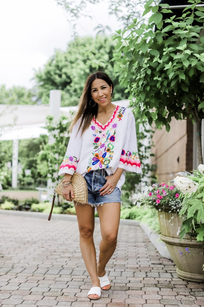 3 Gorgeous Pieces From Paulita Carlotta by top US fashion blog, House of Leo Blog: image of woman wearing embroidered tunic with denim cutoff shorts