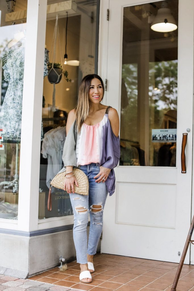 3 Gorgeous Pieces From Paulita Carlotta by top US fashion blog, House of Leo Blog: image of woman wearing silk tie dye cold shoulder top and distressed jeans