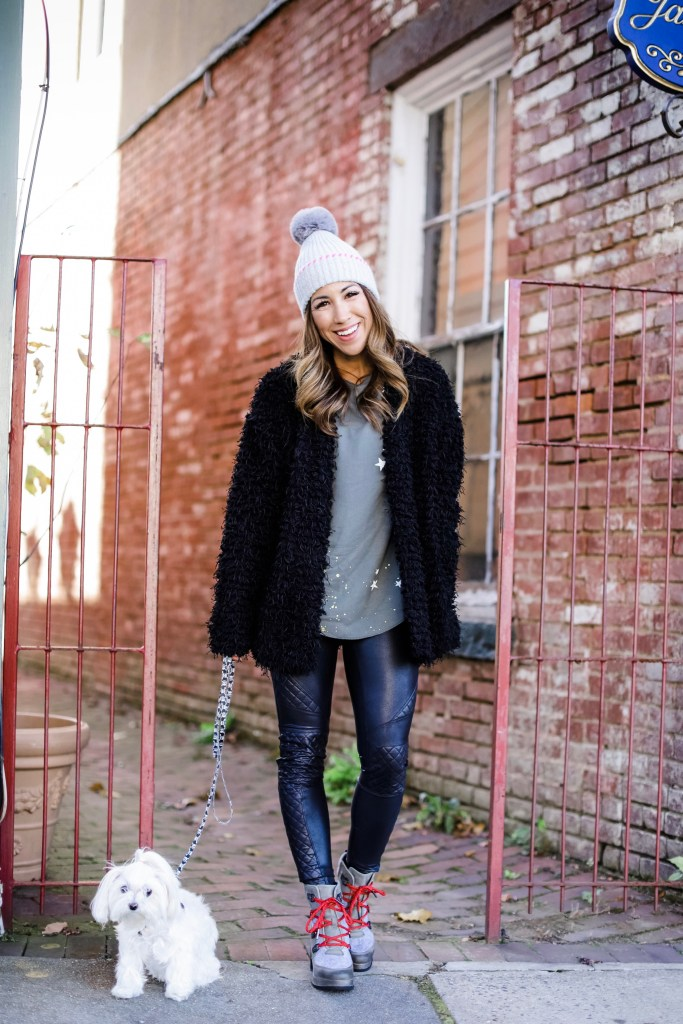 Holiday Outfit Ideas From Evereve by top US fashion blog, House of Leo Blog: image of woman wearing gray star thermal and gray and pink pom pom hat, black quilted Spanx leggings and black faux fur coat