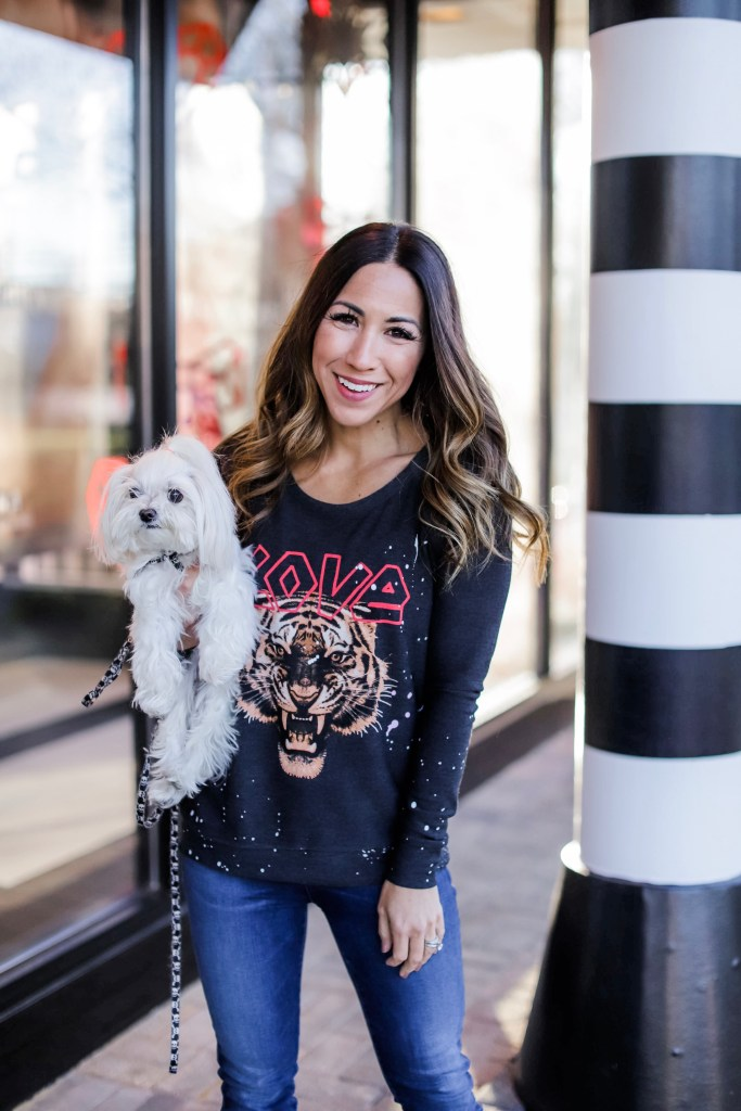 Holiday Outfit Ideas From Evereve by top US fashion blog, House of Leo Blog: image of woman wearing LOVE tiger sweatshirt by Chaser