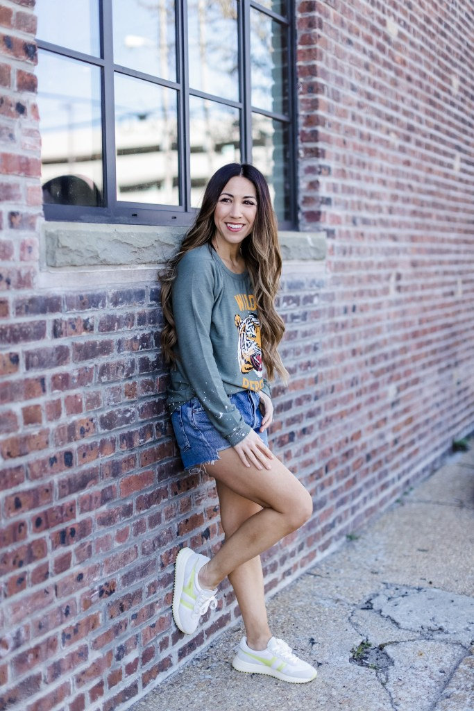 Spring Arrivals From Evereve by top US fashion blog, House of Leo Blog: image of woman wearing Chaser Wild Rebel sweatshirt, Agolde parker shorts and Gola sneakers