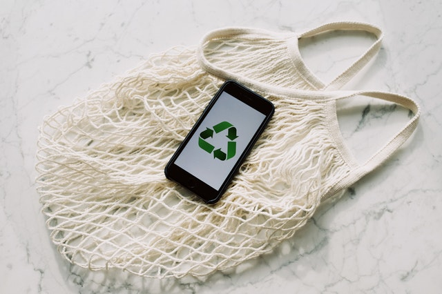 A photo of a reusable bag with a phone showing the reduce reuse recycle symbol