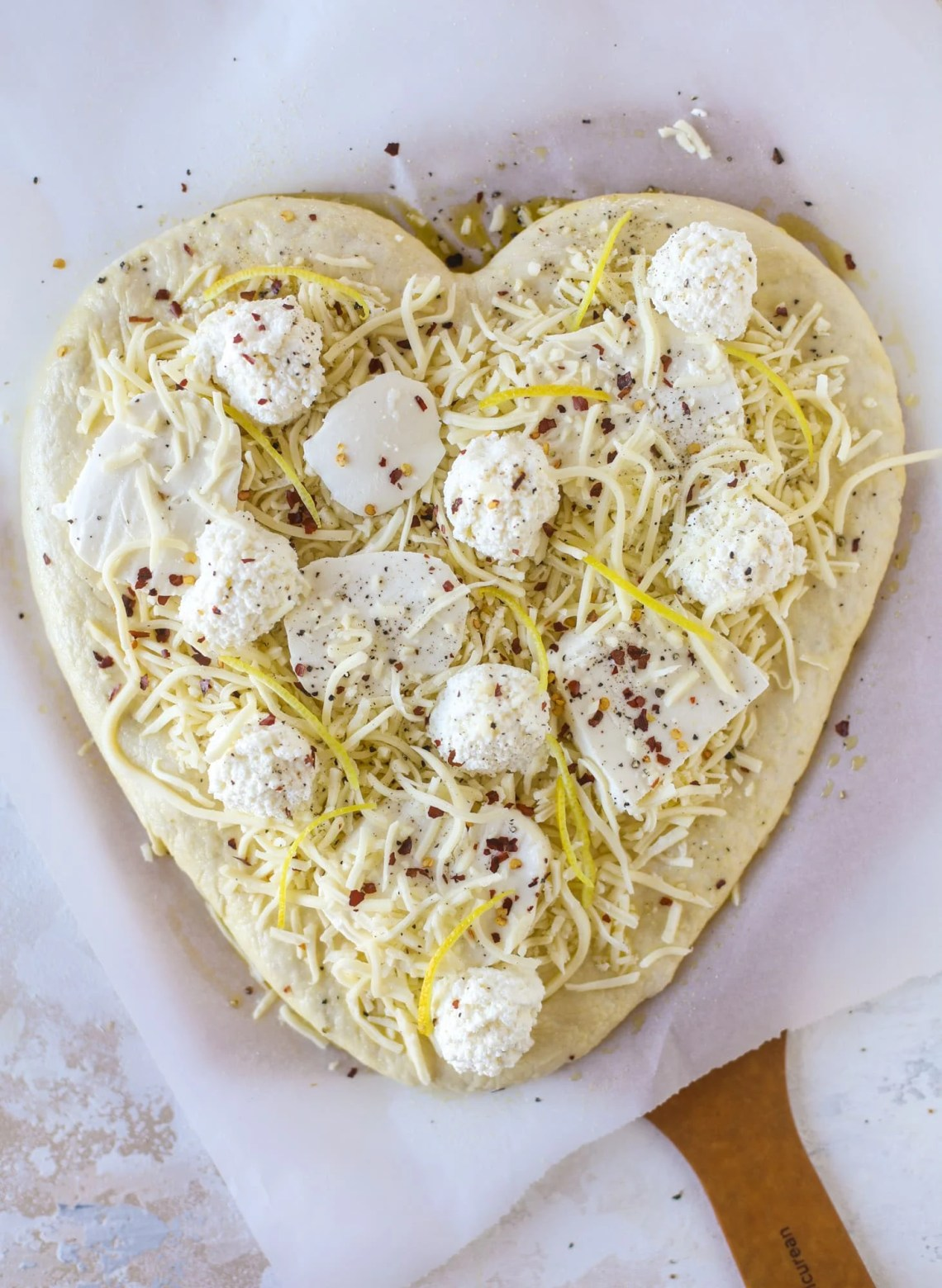Our favorite white pizza recipe has four different kinds of cheese and comes on a garlic bread crust! Topped with crushed pepper and lemon - tons of flavor! I howsweeteats.com #white #pizza