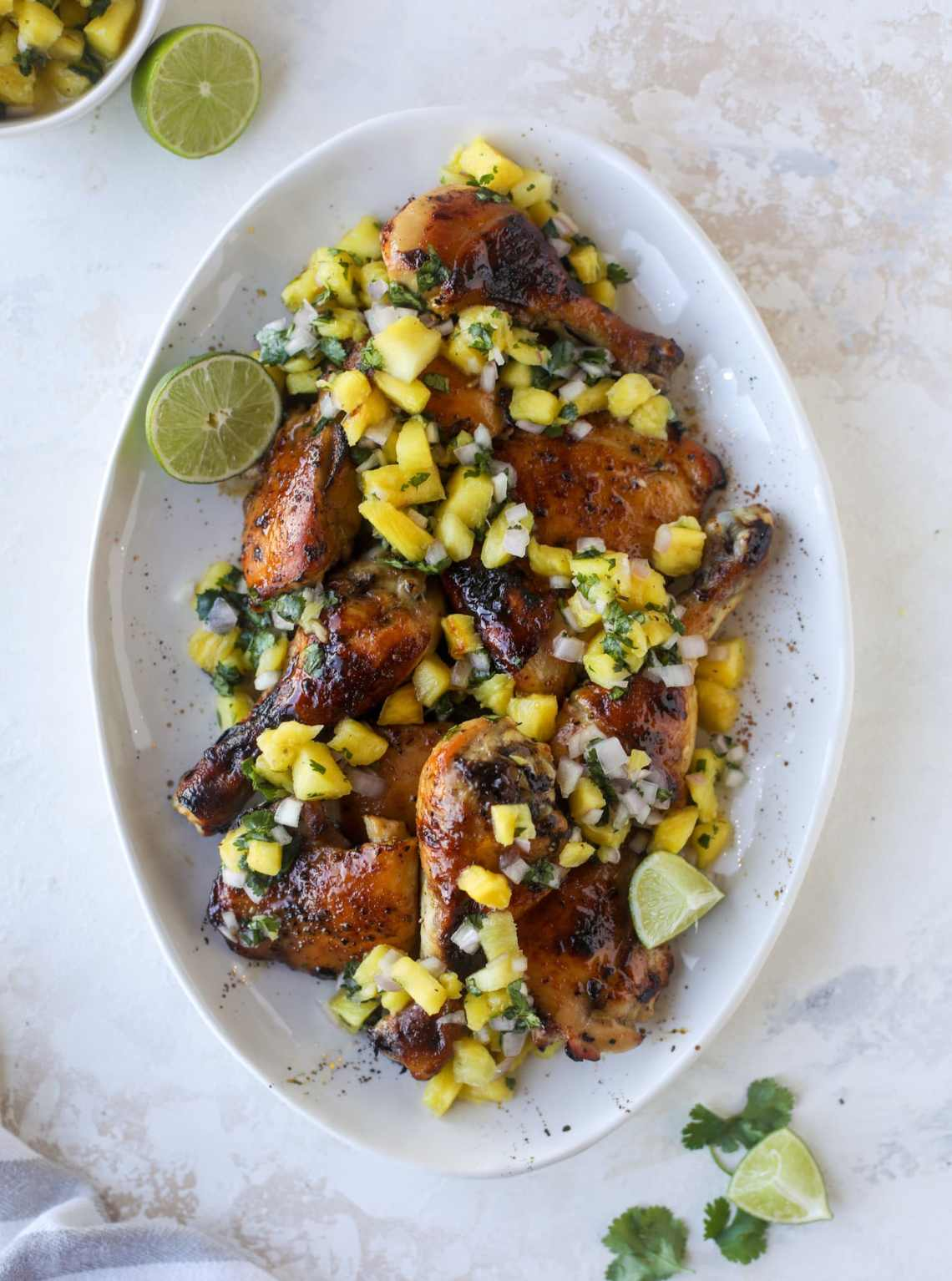 This sticky chicken recipe is made on a sheet pan and roasted until flavorfor and sticky with sauce, then served with pineapple salsa. It's the best! I howsweeteats.com #sticky #chicken