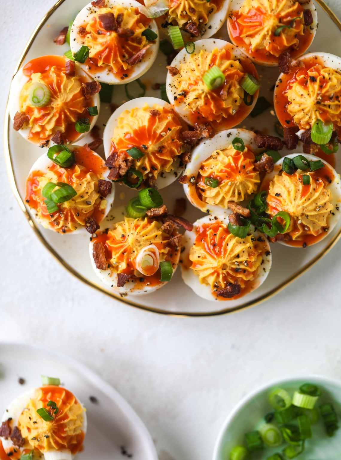 Buffalo deviled eggs are kicked-up deviled eggs! Made with goat cheese filling and served with buffalo wing sauce, crispy bacon and sliced scallions. I howsweeteats.com #deviledeggs #buffalo