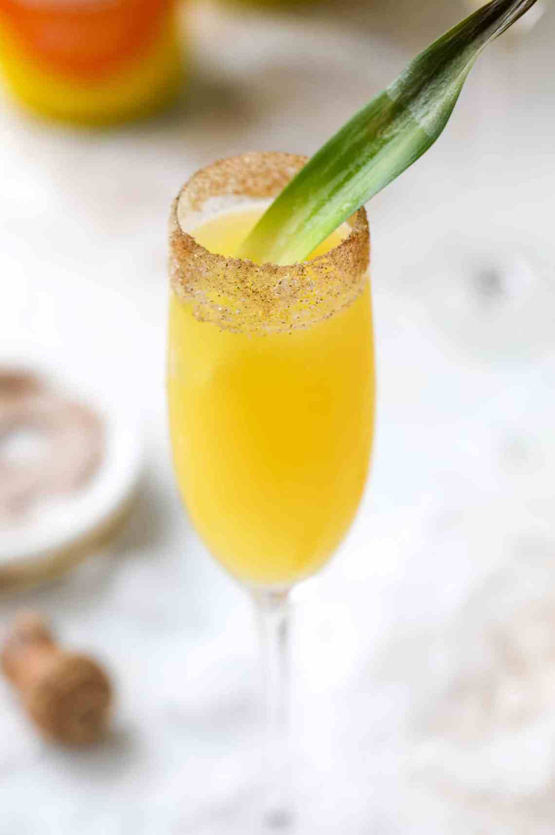 The hummingbird mimosa is a spin on the classic hummingbird cake: pineapple juice, orange juice, champagne and a cinnamon sugar rim! I howsweeteats.com #hummingbird #mimosa