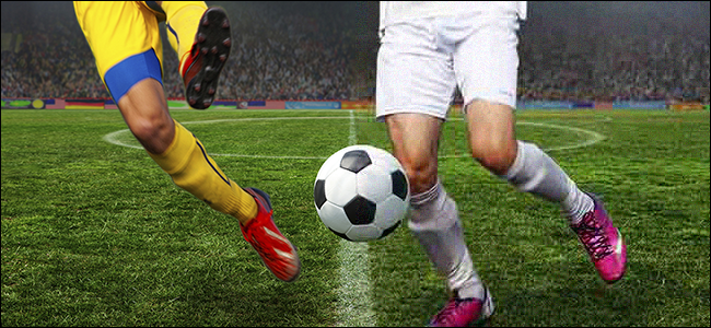 Legs of two athletes playing soccer in a stadium.