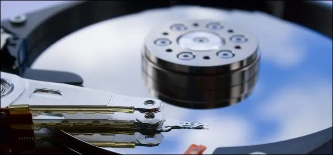 An exposed hard drive platter with the read/write head over top it.