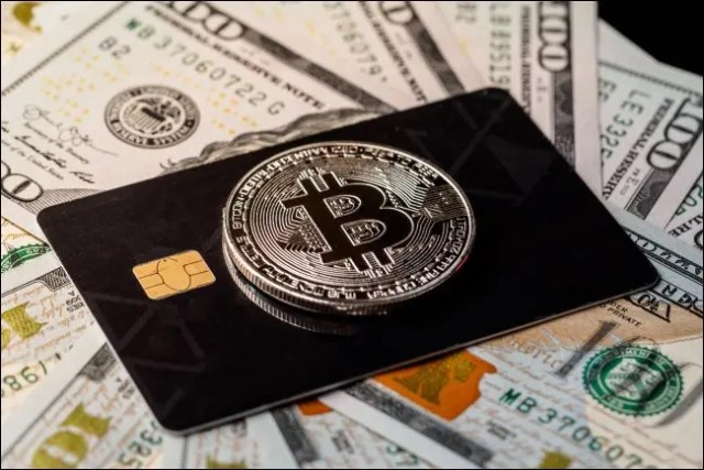 A physical Bitcoin token on top of a credit card lying on $100 bills.