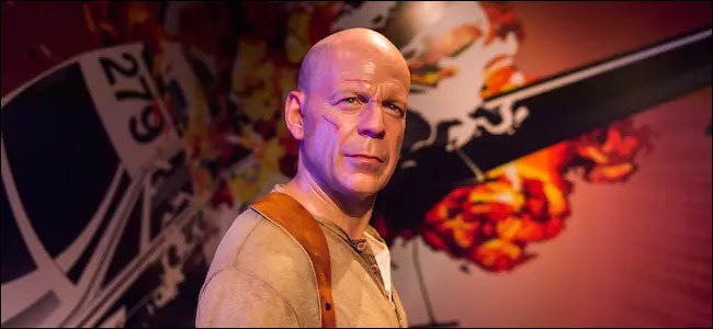Bruce Willis standing in front of an explosion
