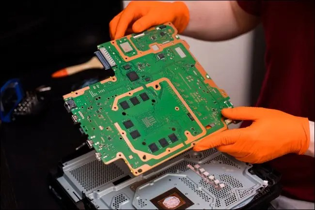 A person repairing the inside of a PlayStation 4 Pro console.