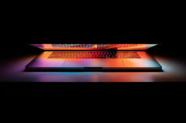 An Apple MacBook Pro partially closed and glowing in the dark.