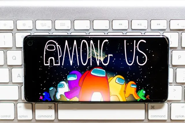 A smartphone on top of a keyboard with Among Us title screen