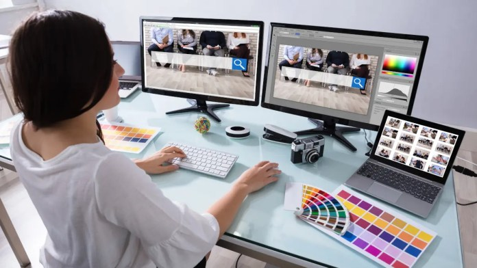 Woman working on web design on multiple computer screens
