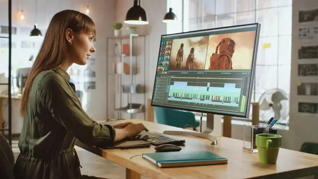 Woman editing videos on a large computer monitor