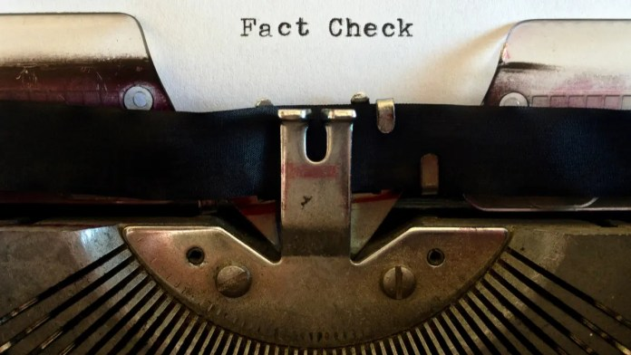 """The words """"Fact Check"""" displayed on a piece of paper in a typewriter."""